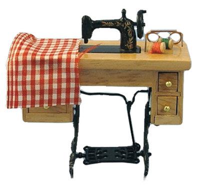 Zwarte naaimachine met naaiwerk en naaitafel